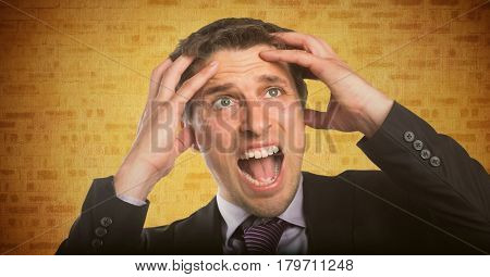 Digital composite of Business man hands on head against yellow brick wall