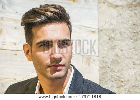 Headshot of handsome young man outdoor in the sun