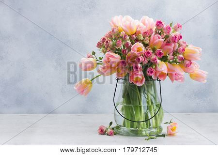 fresh pink and yellow tulips and roses in glass vase on gray background