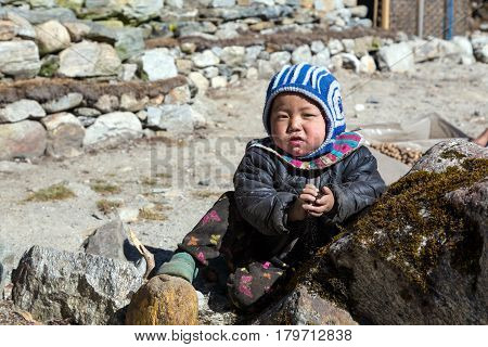 Portrait of little Nepalese Child in remote Himalaya Village playing with pebbles and dirt and looking directly into Camera. Nepal, Solo Khumbu area, November 8, 2016