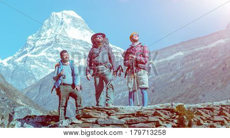 Group of People of different Age and Ethnicity Asian and European young and mature staying on rocky Footpath during Trek in Himalaya Mountains