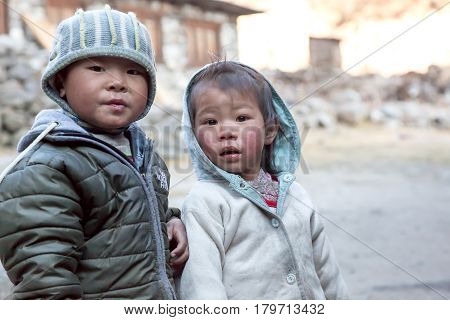 Portrait of little Nepalese Children brother and sister twins, in remote Himalaya Village embracing each other and looking directly into Camera. Nepal, Solo Khumbu area, November 8, 2016