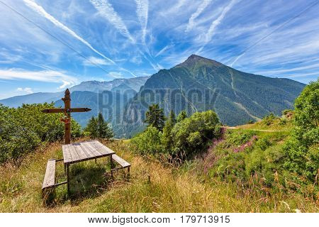 Bench with wooden cross and mountains on background under beautiful sky in Piedmont, Northern Italy.