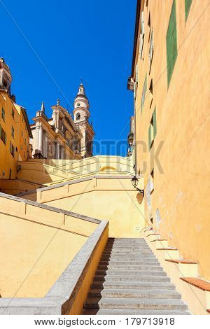 Stairs among colorful walls towards Saint-Michel Archange Basilica under blue sky in Menton, France (vertical composition).