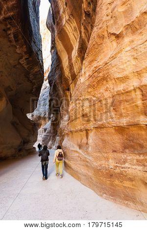 Tourists Walk In Al Siq Passage To Petra Town