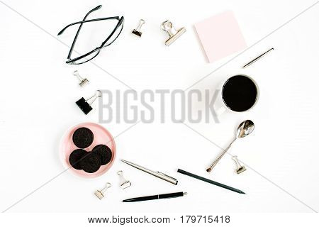 Pale pink home office workspace desk frame with coffee cookies glasses and office stuff on white background. Flat lay top view. Entrepreneur office concept.