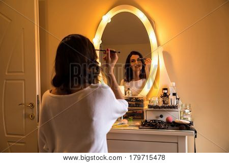 A beautiful young woman sitting at a makeup table and doing her makeup.