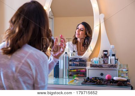 A beautiful young woman sitting at a makeup table and doing her makeup in a bra and a cardigan