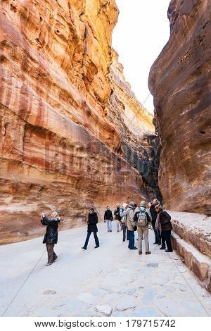 Tourists In Al Siq Pass To Ancient Petra Town
