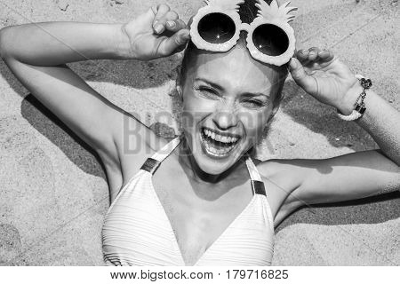 Cheerful Woman In Swimsuit And Pineapple Glasses Laying On Sand