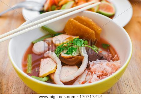 Closeup pink seafood flat noodles (Yen ta fo) Colorful Pink noodle soup with wood background.