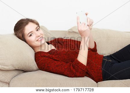 Beautiful girl in red sweater sitting on couch posing and smiling with phone. He speaks on the mobile. Writes a message