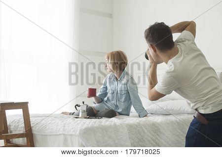 Photographer shooting young model with red cup in her hand on white bed during breakfast
