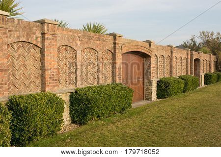 High brick wall with wooden gates shielding garden and large house on seafront at Worthing in West Sussex England
