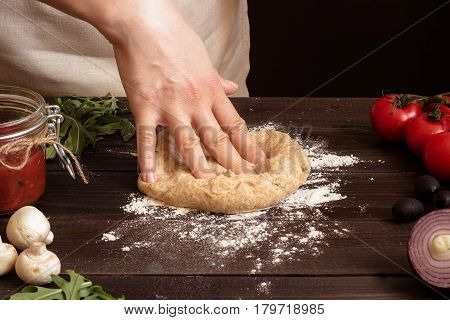 Woman Preparing Dough For Pizza. Hands Kneading Dough On The Wooden Table