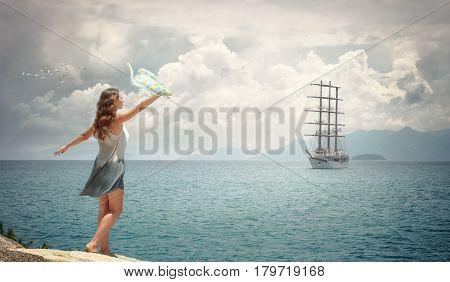 Happy romantic lady meets a sailing ship on the shore waving a handkerchief.