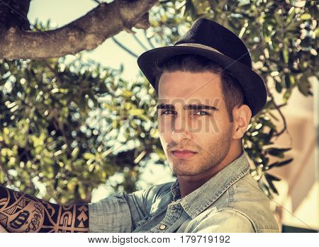 Handsome young man against olive tree branches, looking at camera, in a sunny day, wearing fedora hat