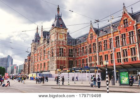 Netherlands, June 2016, Amsterdam: Amsterdam Central train station. the oldest train station in Holland, view of the crowded station the beautiful Dutch and tourists visiting the city on a spring day.