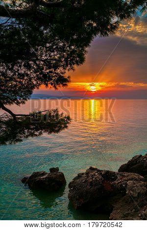 sun setting over the Adriatic sea in a small village Brela Croatia
