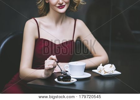 Beautiful woman blonde model in a red jumpsuit fashionable and elegant with a Cup of coffee in the restaurant