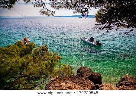 small boats floating near the shore in a small village Brela Makarska Riviera Croatia