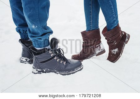 Closeup of male and female legs during a date in winter, shorter woman slid up to reach taller man on love scene, couple kissing