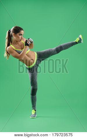 She is a fighter. Vertical shot of a woman in sportswear practicing her kickboxing technique on green background sports activity lifestyle sport fitness muscles toning motivation concept