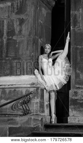 Thoughtful grace. Vertical monochrome shot of a young ballerina posing with her leg up against the wall soft focus