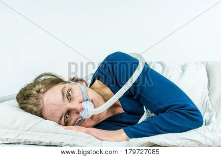 Woman laying on her side with eyes open looking in to camera. CPAP, sleep apnea treatment. Studio portrait white background.