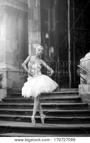 Dancing in the sunlight. Young talented ballerina dancing on the stairway soft focus monochrome shot