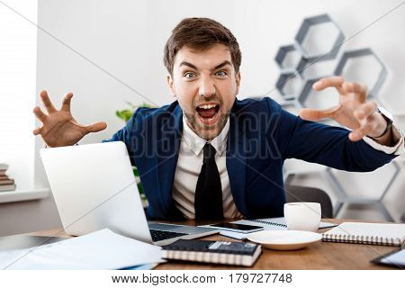 Angry young businessman in suit sitting at workplace, looking at camera, office background.