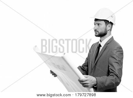 Examining blueprints. Handsome young male businessman architect in a hardhat holding blueprints posing isolated on white copyspace monochrome shot business profession builder worker career concept