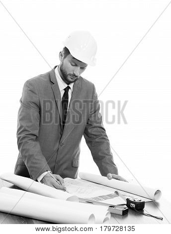 Foreman on work. Black and white vertical studio shot of a handsome professional male constructionist wearing protective helmet working on a building plan professionalism developer businessman