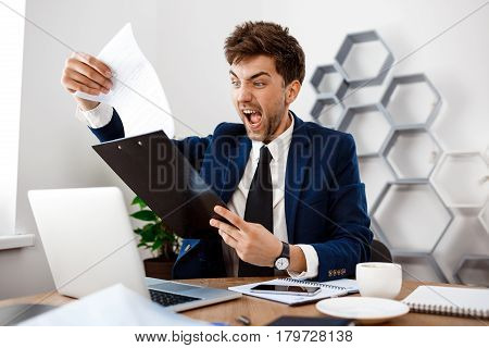 Angry young businessman in suit sitting at workplace, looking at folder with papers, shouting, office background.