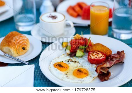 Delicious breakfast with fried eggs, bacon and vegetables
