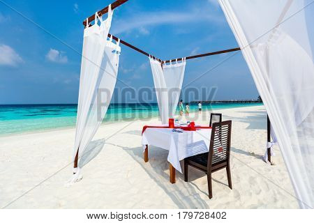 Romantic luxury dinner or lunch setting at tropical beach in Maldives