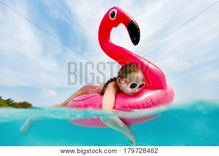 Split underwater photo of adorable little girl with pink flamingo inflatable ring swimming in a tropical ocean on summer vacation