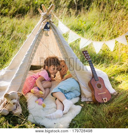 Children lie in the wigwam in the nature