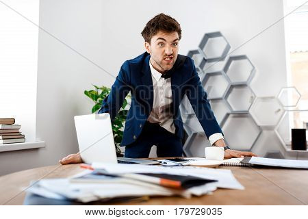 Angry young businessman in suit standing at workplace, hands on table, office background.