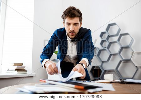 Absentminded young businessman in suit rummaging in papers at workplace, office background.