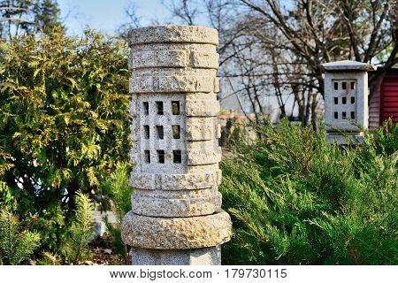 Stone lantern decorations in Japanese garden against green plants.
