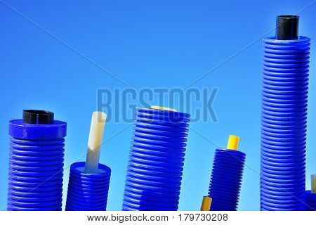 Colorful new bright Industrial plastic pipes with thermo isolation for outdoor water line or driving underground against bright sky blue background.