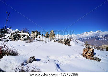 Buddhist chortens covered snow above Muktinath Himalaya rang rising in the babkground. Nepal.