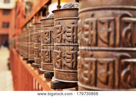 Line of vintage copper praying drums with sanskrit symbols