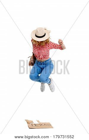 Portrait of young beautiful country girl in hat, jeans and shirt hitchhiking, jumping over white background.