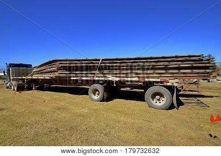 A truck load of salvaged rafters are loaded unto a flat bed semi truck and trailer