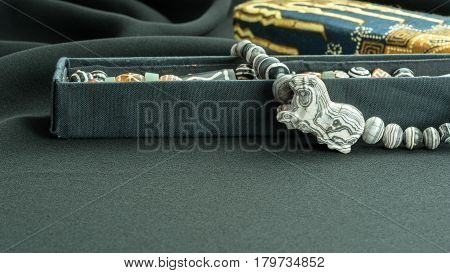 Close up ancient rare carved tiger agate bead in agate necklace on black cotton fabric background