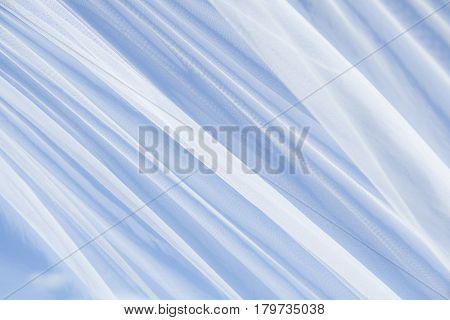 Soft Tulle fabric Background Texture. Decorative Transparent white textile on the blue background. Beautiful Horizontal Wallpaper with selective focus