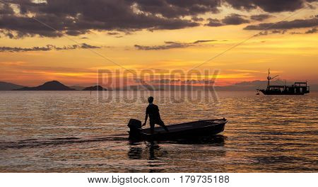 Silhouette of one fisherman on a small fishing boat with outboard motor on the ocean at nightfall with an orange sunset and another boat at the background in asia.