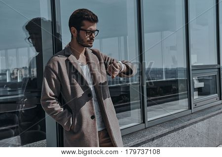Just in time. Confident young man in eyewear checking the time while leaning on the office building outdoors